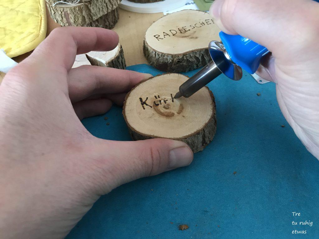 Mit dem Brandmalkolben die Holzscheiben beschreiben