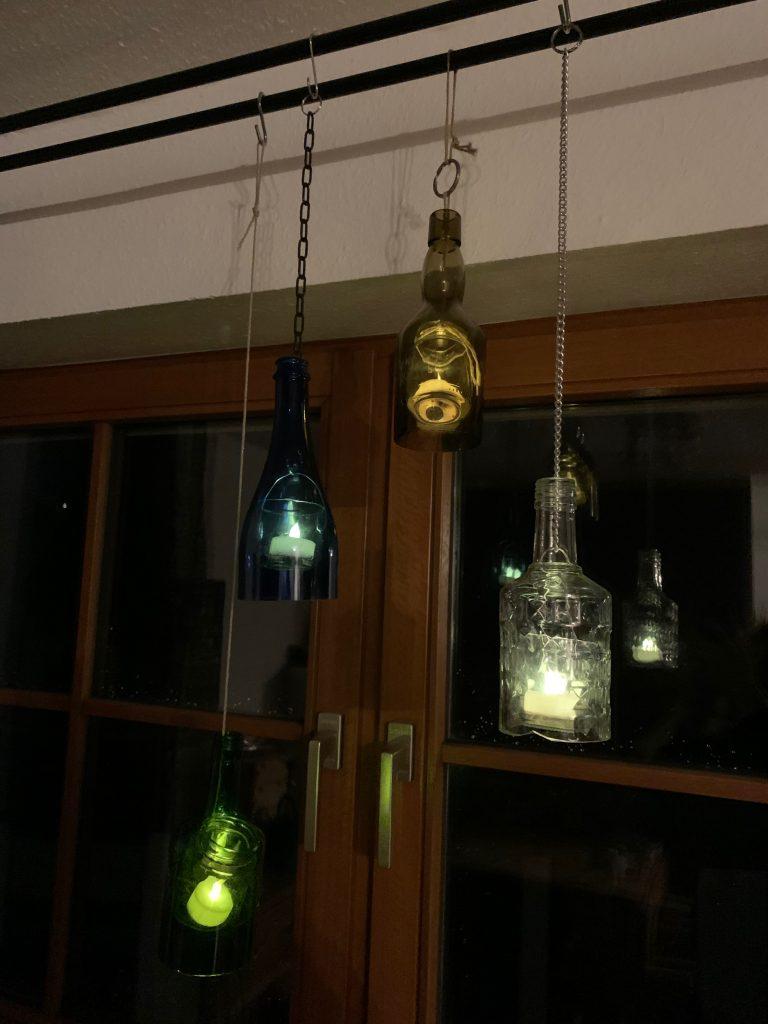 Oberteile von Glasflaschen als Laternen mit LED-Teelichtern