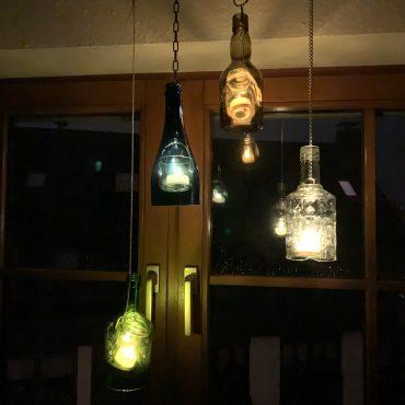 Hängende Laternen aus Glasflaschen