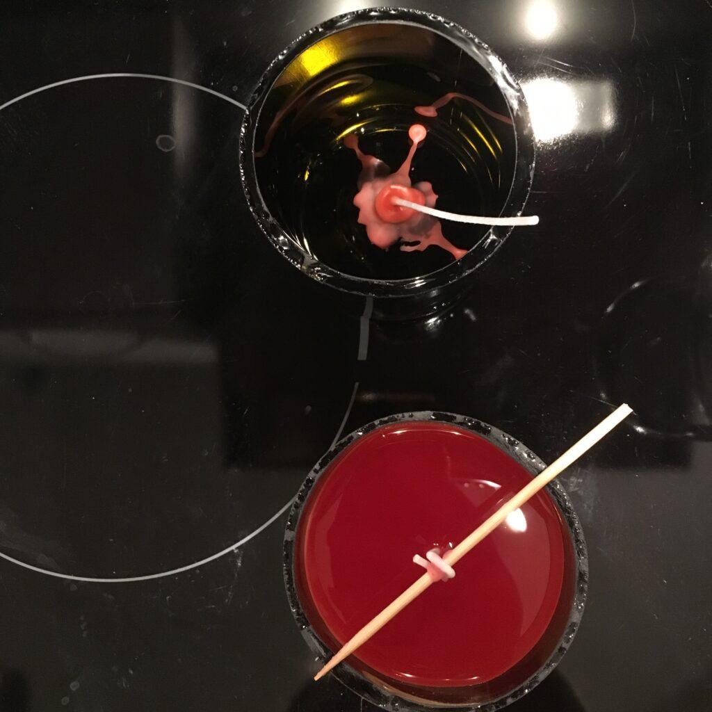 Fixierter Docht und frisch gegossene Kerze im Glas in Rot